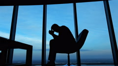 Silhouette of sad, unhappy businessman sitting on armchair by the window. Stock Footage