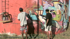 Two young men painting graffiti on wall Stock Footage