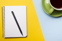 Office desk table with supplies top view. Notepad, pen and colorful paper. Copy - stock photo