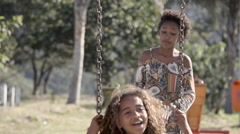 A teenage girl swinging her friend on swing Stock Footage