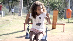 Girl swinging on a swing in a park Stock Footage