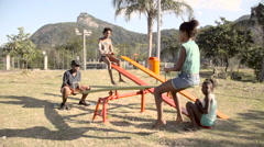 Teenage kids playing on seesaw in a park - stock footage