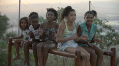 Five teenage girls sitting on a railing, clapping and singing Stock Footage