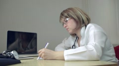 Doctor Fills Out a Medical Form in the Office Stock Footage