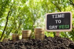Time to say Yes. Financial opportunity concept. Golden coins in soil Chalkboard - stock photo