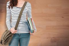 Composite image of mid section of man with should bag and files - stock photo