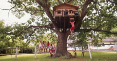 Children in a treehouse with boy climbing up rope ladder Stock Footage