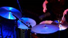 The drummer plays at a concert in a dark club beats the drums sticks. Stock Footage