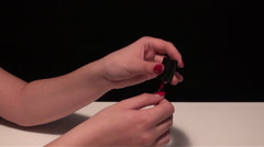 Young woman painting her nails red. On a white table. Black background Stock Footage