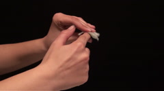 Young woman cleaning his fingernails with nail polish remover. Black background Stock Footage