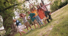 Mixed race person of boys and girls with soccer ball Stock Footage