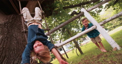 Little boy hanging from a rope ladder smiling at camera Stock Footage