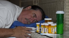 Sick man looking at many bottles of prescription pills Stock Footage
