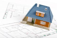 Real estate development - house scale model on blueprints Stock Photos