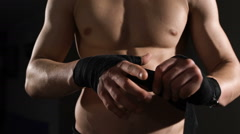 Close-up mid section of a shirtless muscular man binds bandage on his hand - stock footage
