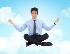 Composite image of asian businessman doing yoga Stock Photos