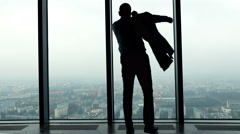 Silhouette of businessman dressing up suit jacket by the window in the office Stock Footage