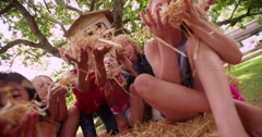 Children blowing straw on hay bales under a wooden treehouse - stock footage