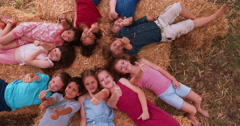 Multi ethnic Group of children lying in circle on hay Stock Footage