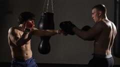Artful young kickboxer fulfills blows with coach Stock Footage