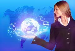 Business woman holding a globe on his hand with rotating icons Stock Photos