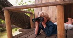 Boy lying in a treehouse looking through binoculars - stock footage