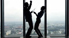 Silhouette of  successful businesspeople with tablet computer and smartphone Stock Footage