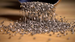 Pouring chia seeds onto wooden table, slow motion Stock Footage