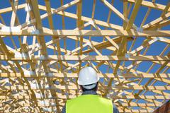 Construction worker looking at the roof of a house under construction Stock Photos