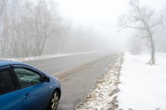 Blue car on a foggy road Stock Photos