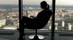 Silhouette of young businesswoman working on laptop on armchair in the office Stock Footage