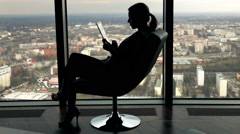Stock Video Footage of Silhouette of young businesswoman working on tablet computer sitting by armchair