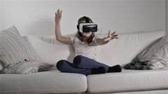 Girl wearing virtual reality goggles. Studio shot, white couch - stock footage