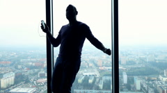 Silhouette of man dancing while listening to music by window with city view - stock footage