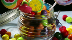 Colorful candies in jar on wooden background Stock Footage