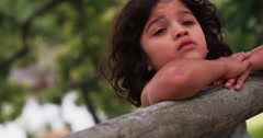 Little hispanic boy leaning on a rustic wooden fence thinking - stock footage