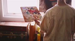 Artist painting on canvas with fine brush in her studio - stock footage