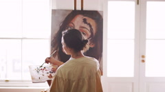 Woman artist working on canvas in a studio with windows Stock Footage