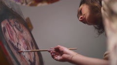 Artist painting on a canvas with brush and palette - stock footage
