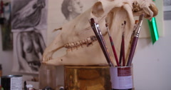 Artist paintbrushes in a mug on table in art studio - stock footage