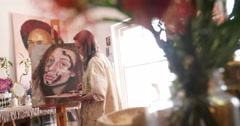 Artist in her studio painting a canvas on an easel Stock Footage