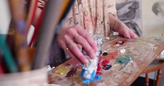 Paint covered hands of an artist in smock holding paintbrushes Stock Footage