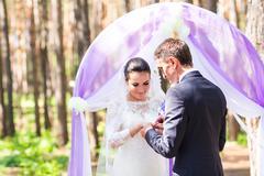 Elegance groom putting on wedding ring his bride. Wedding ceremony Stock Photos