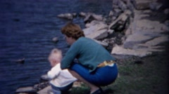 1962: Mother baby enjoy lakeshore water summer rock throwing. Stock Footage