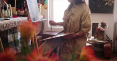 Artist painting a canvas in her real and messy studio - stock footage