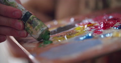 Vibrant multi colored paints on a palette mixed with knife Stock Footage