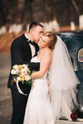 Stylish wedding couple, bride, groom kissing and hugging near retro car in - stock photo