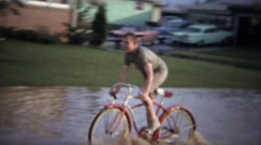 1961: Kids riding bike thru flooded street in stagnant sewage water. - stock footage