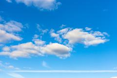 blue sky with clouds and horizontal airplane trail - stock photo