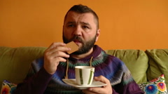 Man drinking coffee and eat sweet cookie at home    Stock Footage